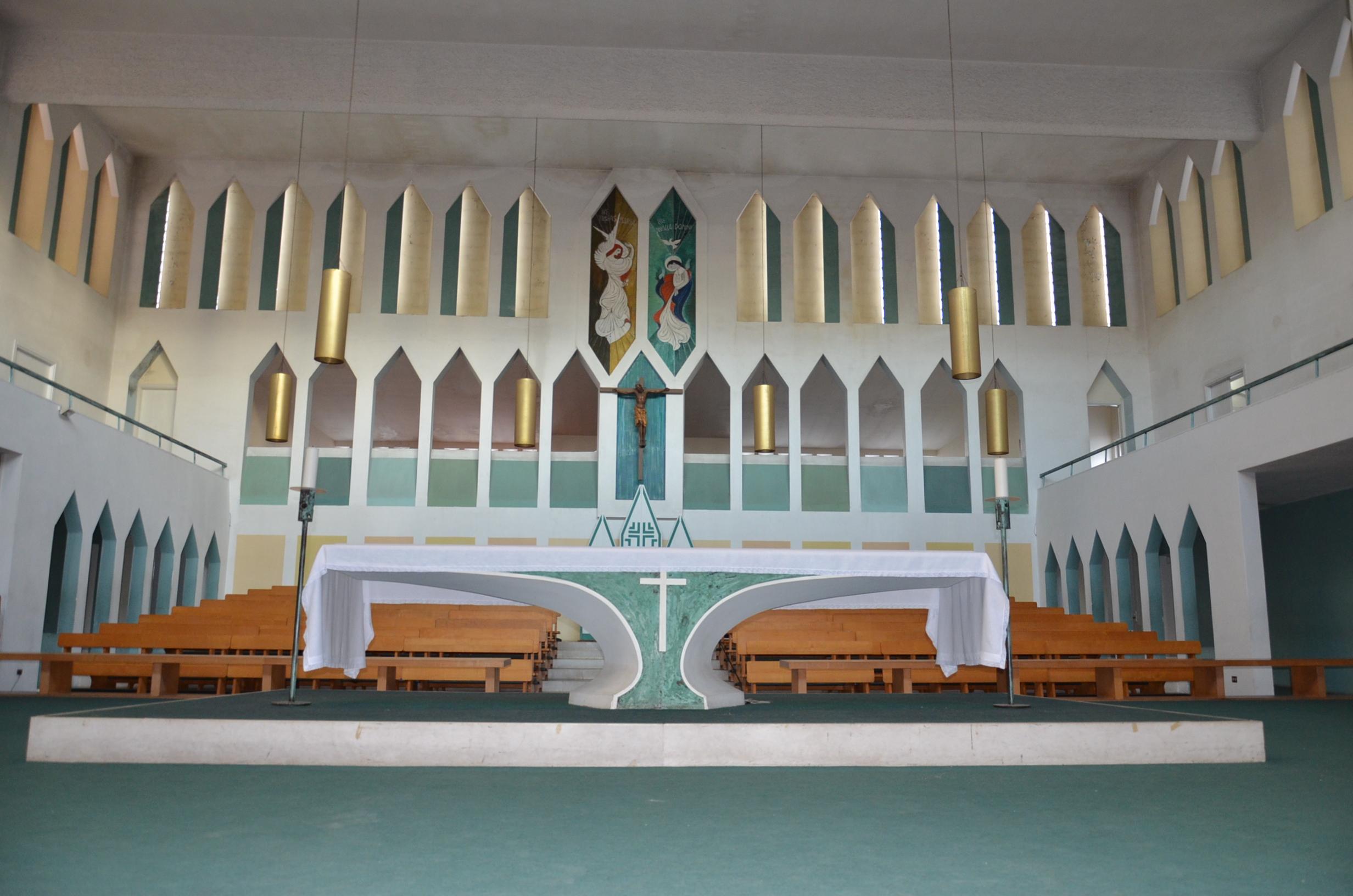 La pedana dell'altare attraversa l'aula ecclesiale. Al centro della parete di fondo sta la cattedra. Le pareti sono attraversate dalla figura del diamante, in un ritmico dispiegarsi su vari livelli. (foto C. Giordano)