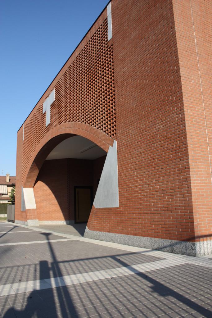 """L'elaborazione del portale. Inserti in cemento sono motivi espressivi, a partire dalla croce a """"tau"""" che sovrasta l'arco."""