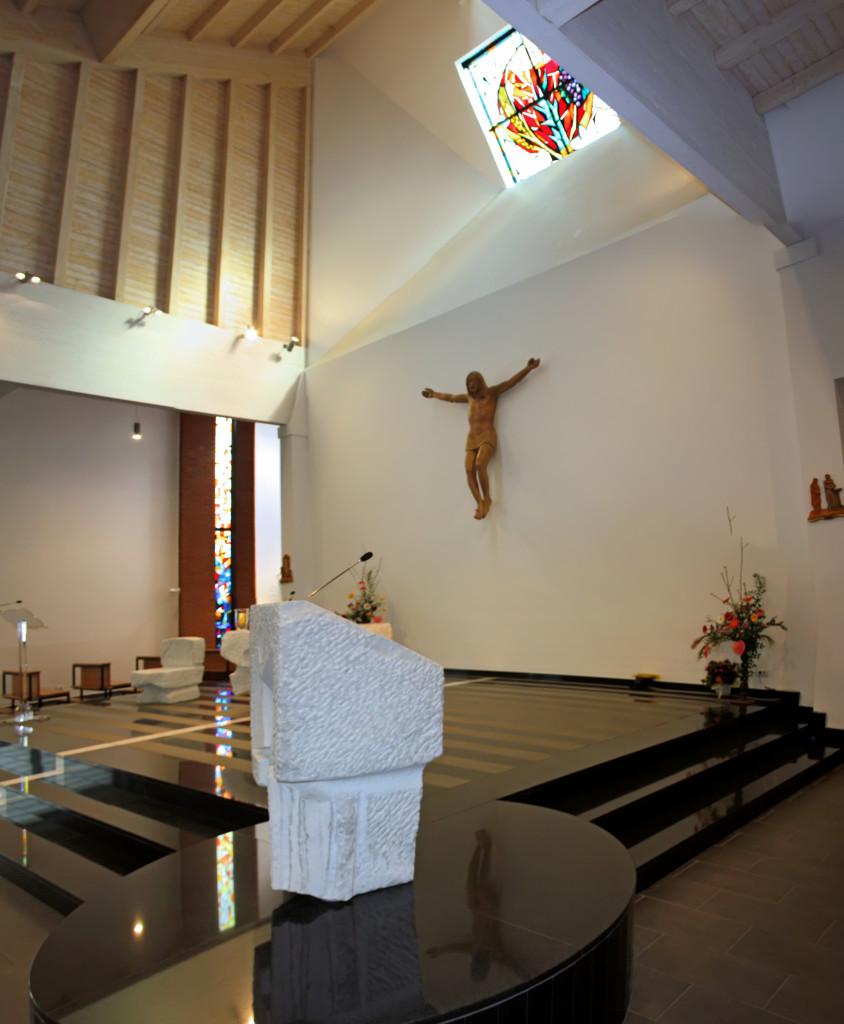 La pedana dell'altare. Inpirmo piano l'ambone. SUlla parete il crocifisso ligneo e, sopra, la grande vetrata.