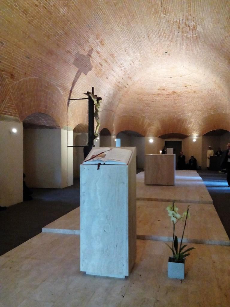 La disposizinoe liturgica della cappella si fonda su una lunga pedana al cui centro sta l'altare, da un lato l'ambone e dall'altro la custodia eucaristica.