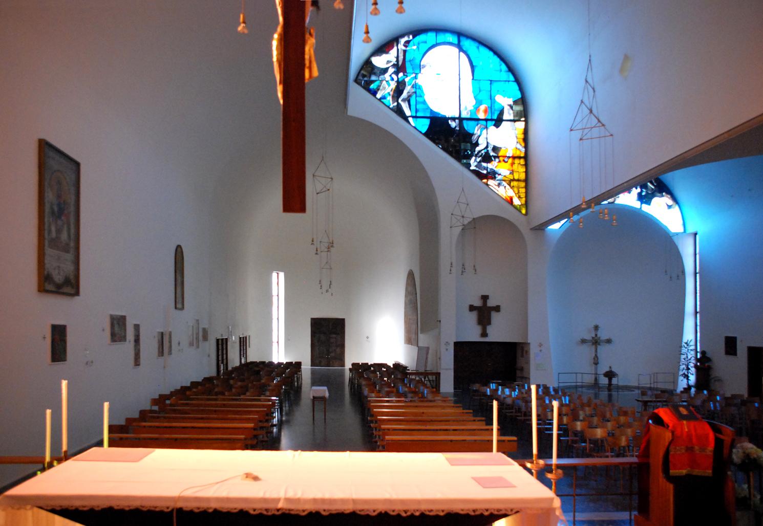 La vista dall'altare verso l'ingresso evidenzia il battistero a destra, sul retro dello spazio riservato alla cappella laterale. Una posizione defilata ma visibile e prossima all'ingresso.
