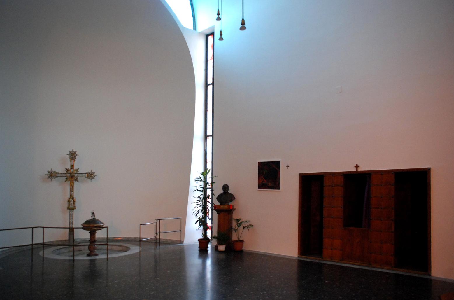Abside e vetrata inquadrano e nobilitano lo spazio del battistero, prossimo al quanle è posto il confessionale. La vasca è a pavimento, semplice e tonda. La simbolicità è affidata all'elaboraizone spaziale dell'insieme (foto Andrea Longhi).