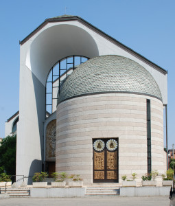 L'ingresso pirncipale, a sinistra del quale di nota di scorcio un'altra abside: quest'ultima ospita il battistero. Nella pianta (sotto) si apprezza la disposizine dei poli liturgici nell'architettura poliabsidata.