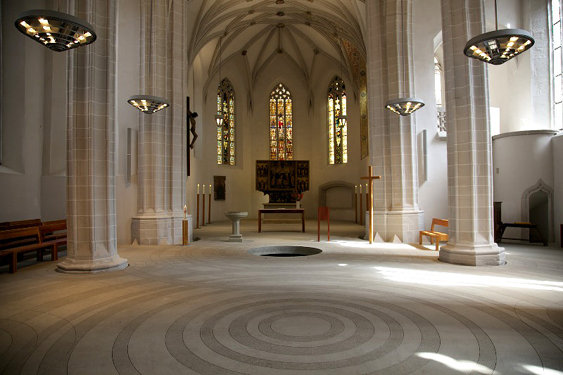 La prospettiva frontale evidenzia il rapporto tra spazio battesimale e altare, olte il quale si notano le vetrate absidali verso oriente.
