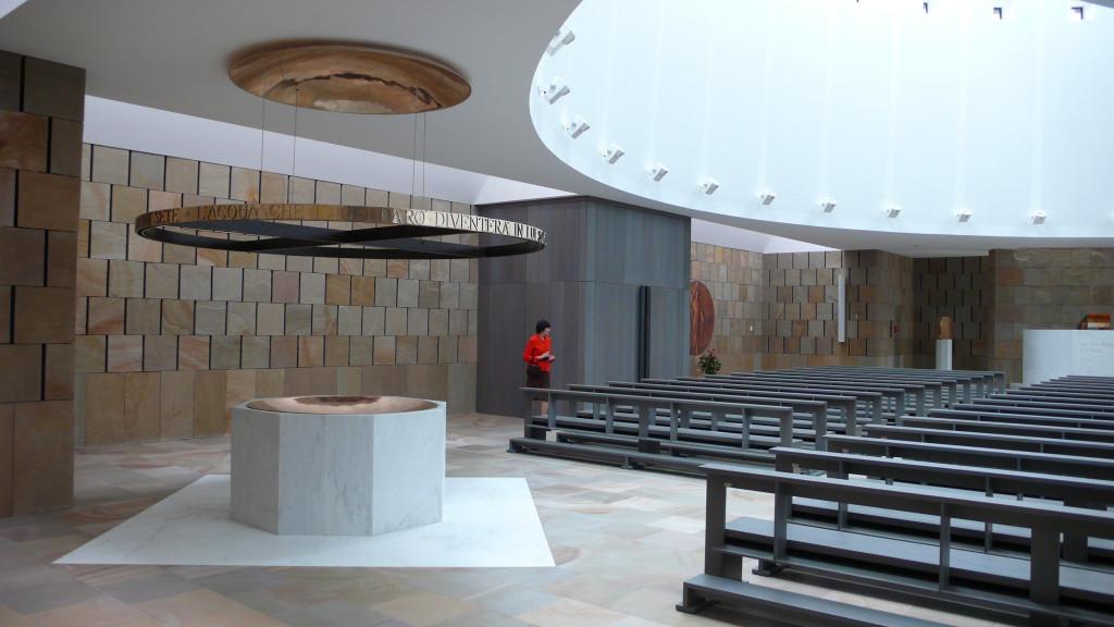 Il fonte battesimale è ottagonale e un cerchio sospeso ne evidenzia la presenza. Si trova a sinistra dell'ingresso delal chiesa.