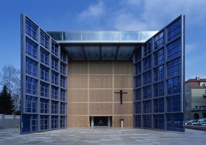 Il volume esterno trasparente contiene all'interno la chiesa in lamelle lignee. Il percorso tra porta e altare è lineare.